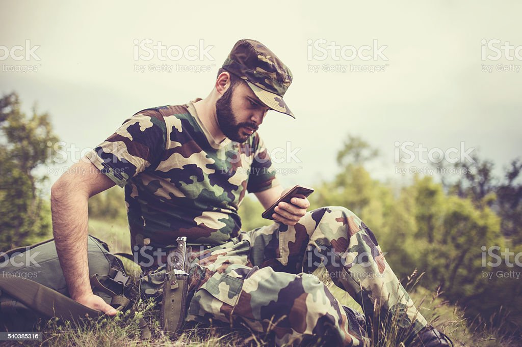 Soldier resting with smart phone stock photo