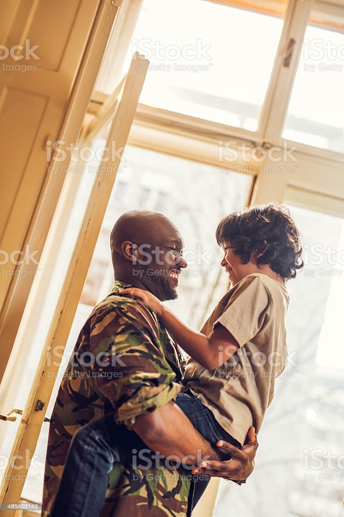 Soldier reunited with his son after coming back from war. stock photo