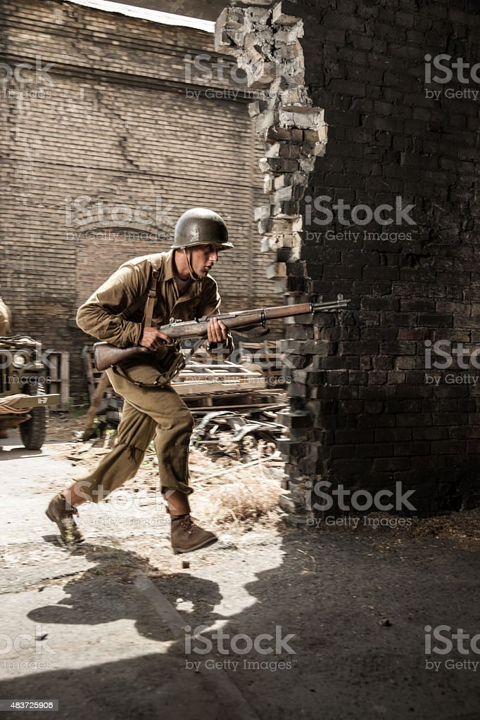 WWII Soldier Running Into Building Under Attack stock photo