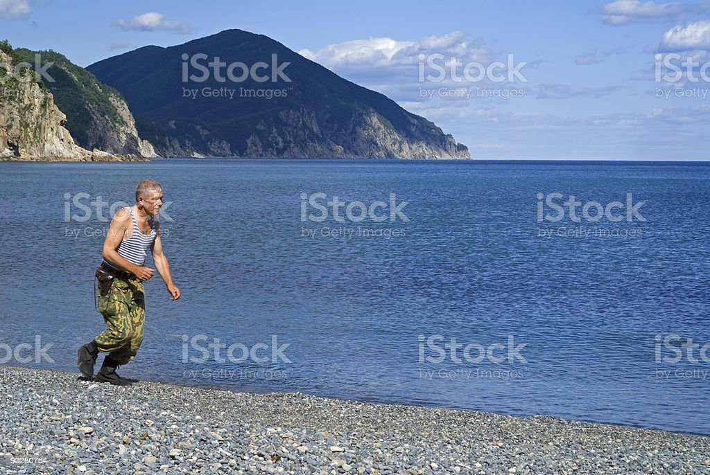 Soldier runs at sea stock photo