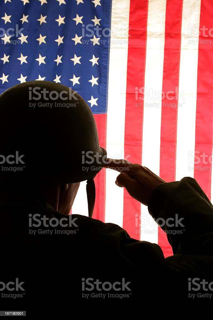 WWII Soldier Salutes USA flag wearing field dress uniform. America. royalty-free stock photo