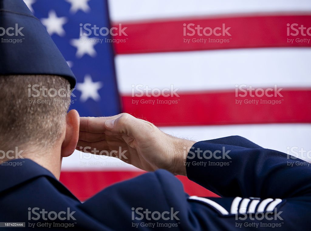 Soldier saluting American flag stock photo