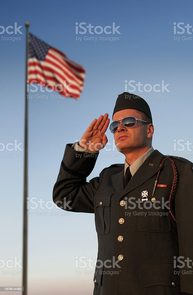 US Soldier Saluting in Front of American Flag stock photo