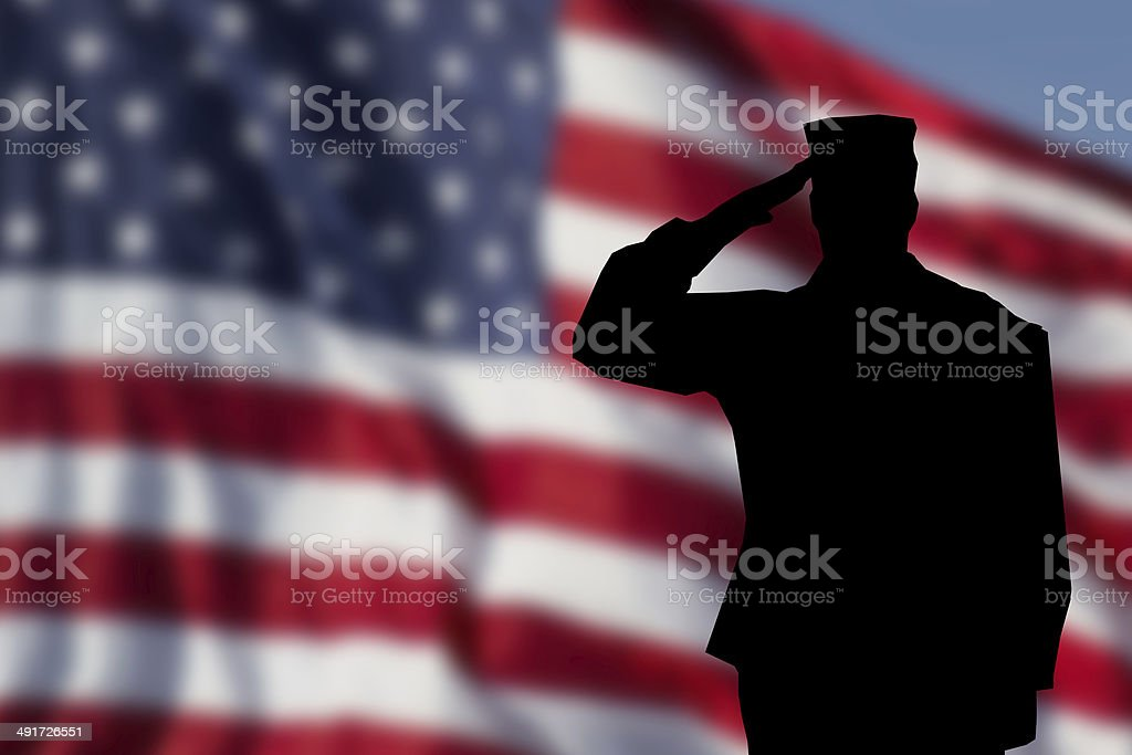 Soldier saluting the USA flag for memorial day stock photo