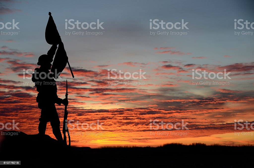 Soldier silhouette carrying a flag across a field at sunset stock photo
