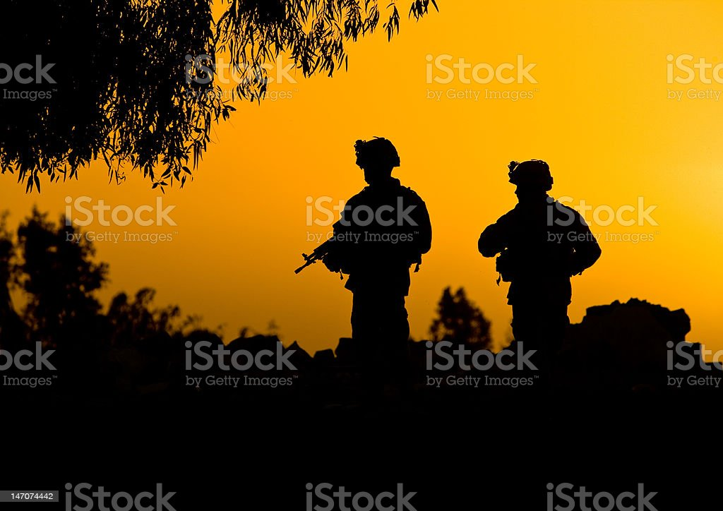 Soldier silhouettes in sunset stock photo