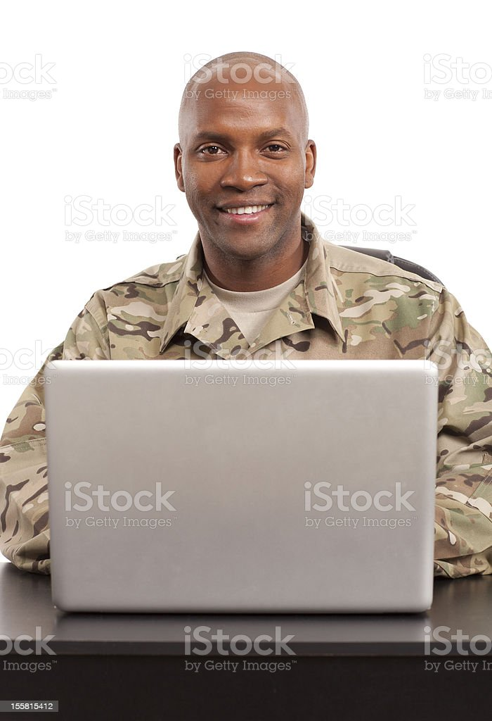 Soldier smiles while working on a computer royalty-free stock photo