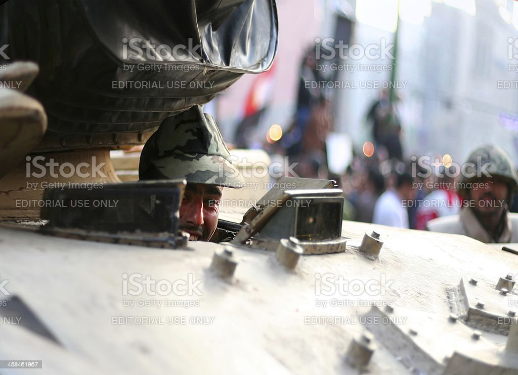 soldier smiling behind a tank stock photo
