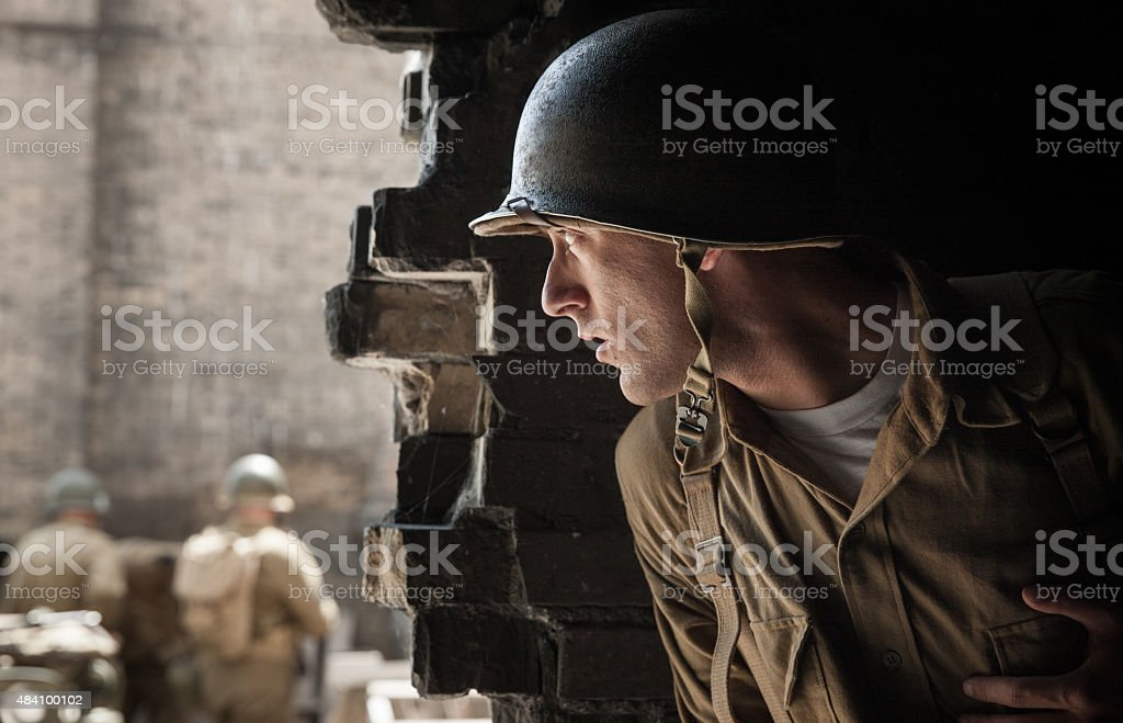 WWII Soldier Spy Hiding Behind Wall stock photo