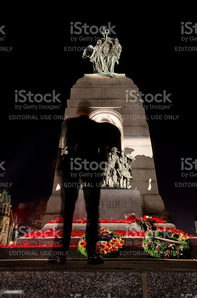 Soldier standing in front of Remembrance Day Memorial stock photo