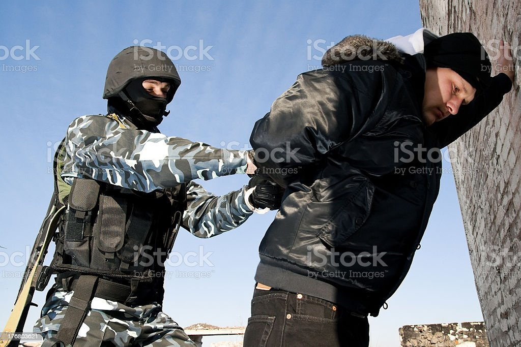 Soldier taking a criminal under arrest royalty-free stock photo