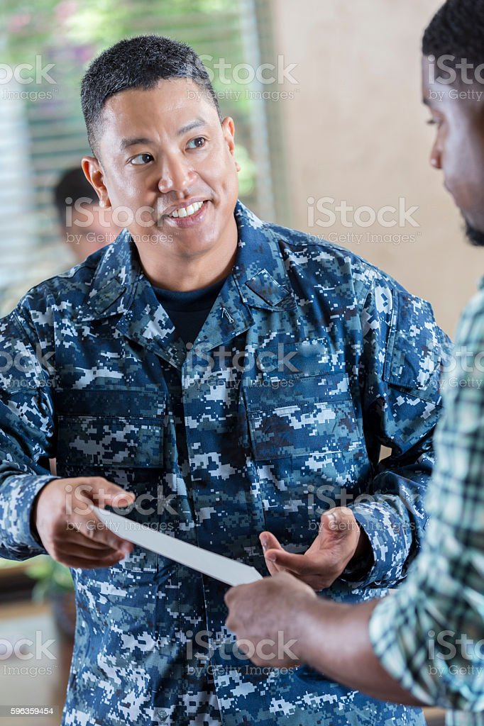 Soldier talking to young man at armed forces recruitment event stock photo