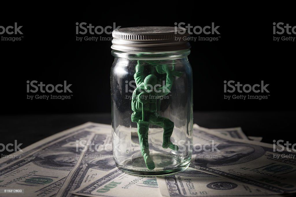 Soldier toy in bottle on money. stock photo