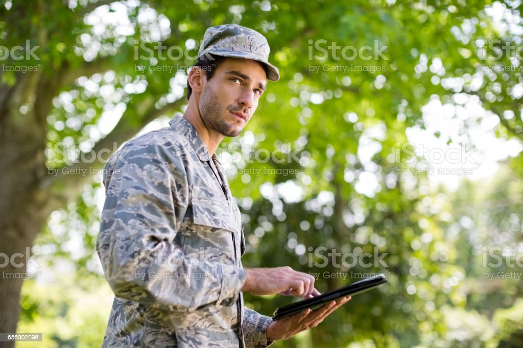 Soldier using digital tablet in park stock photo