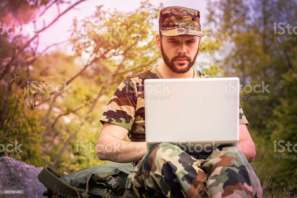 Soldier using laptop stock photo