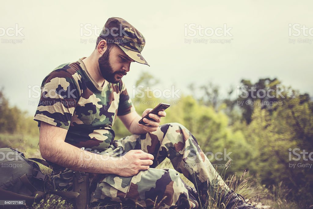 Soldier using smart phone stock photo