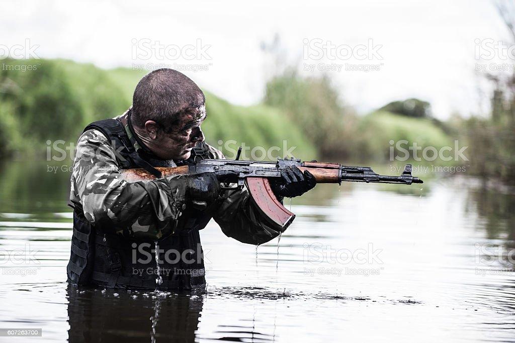 Soldier wades through deep water under a bridge stock photo