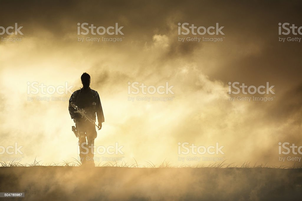 Soldier Walks Away from Dramatic Firey Horizon stock photo