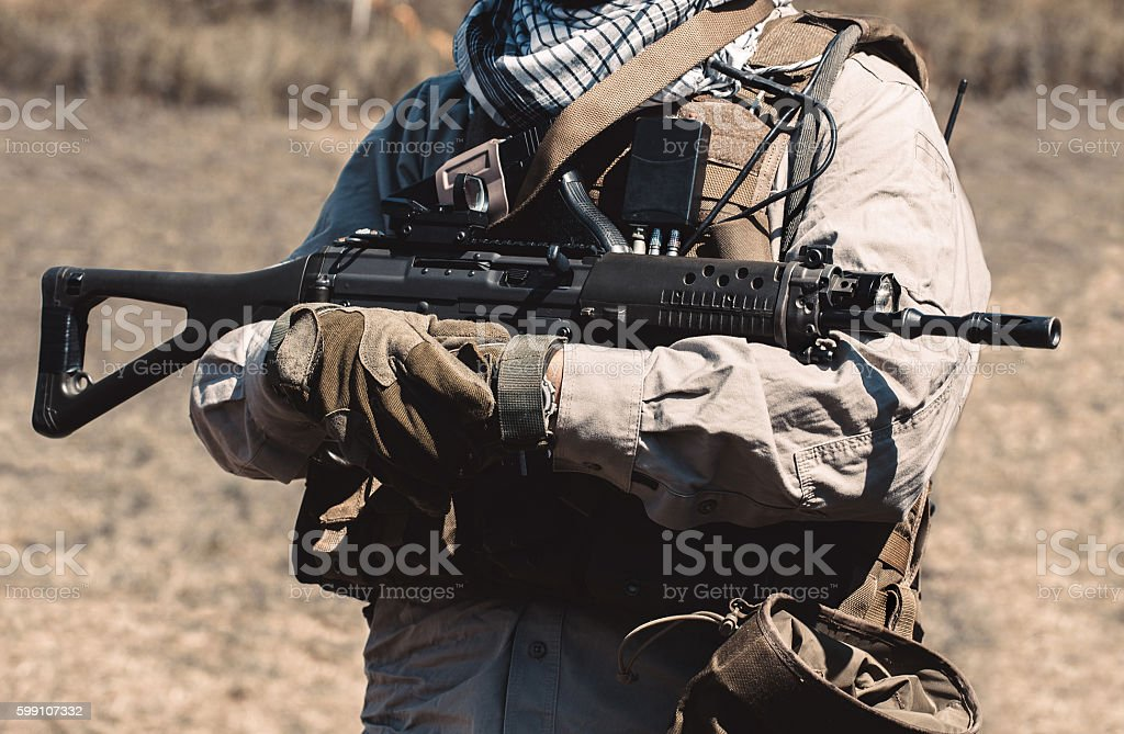 soldier wearing a vest holding an assault rifle. stock photo