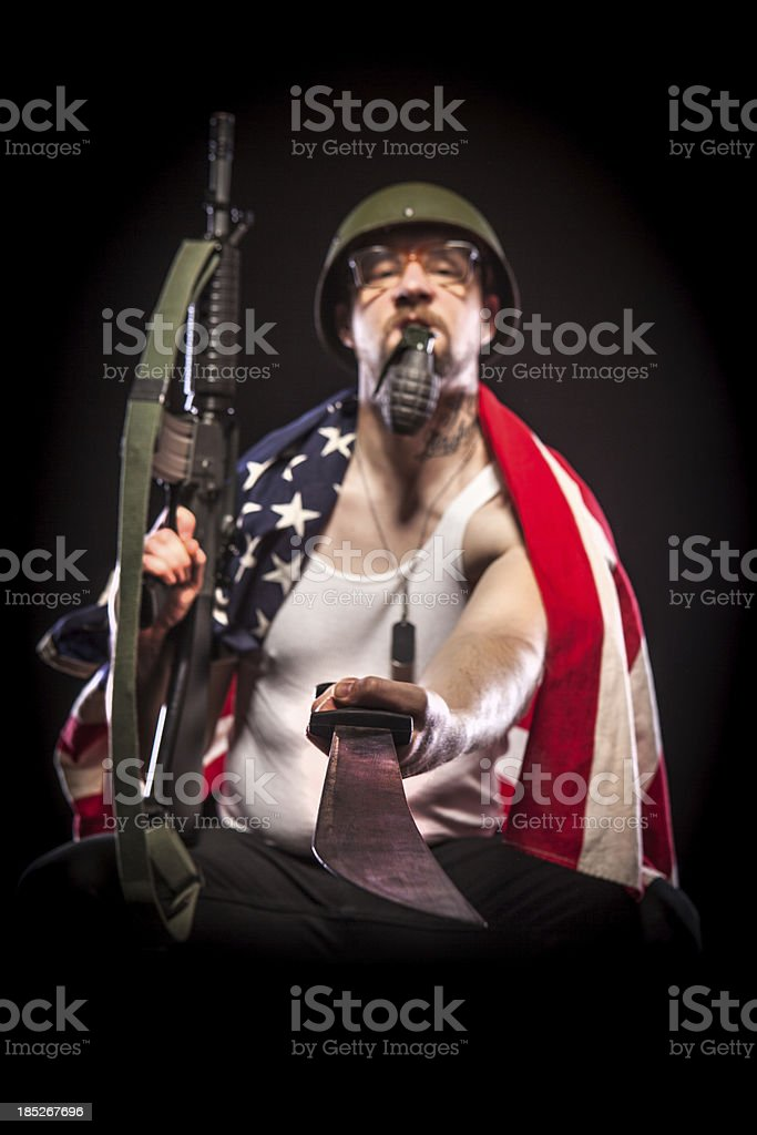 Soldier Wearing American Flag, Holding Grenade in Mouth, Machete stock photo