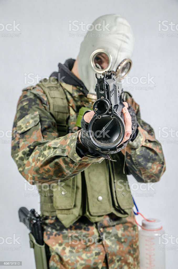 Soldier wearing gas mask aiming gun at camera stock photo