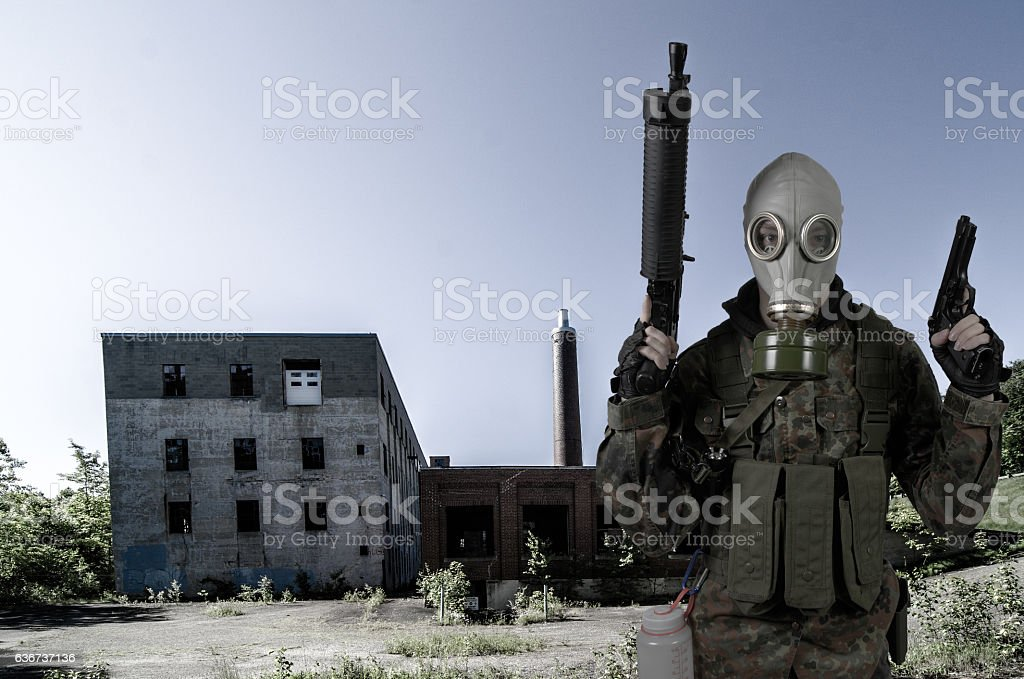 Soldier wearing gas mask holding guns in front of factory stock photo
