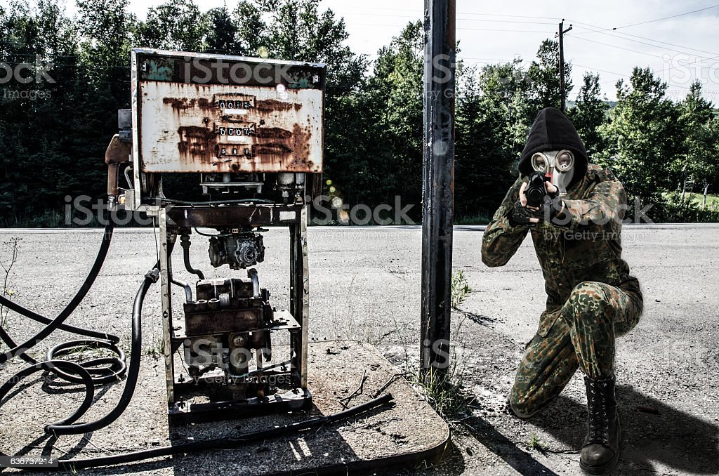 Soldier wearing gas mask protecting gas station with shot gun stock photo