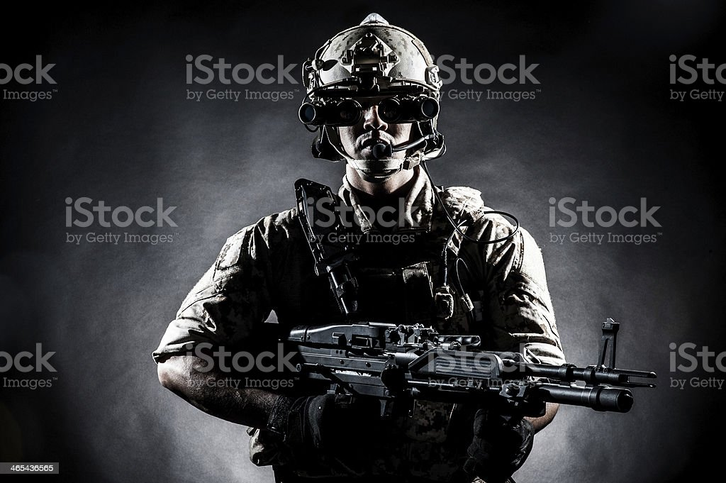 Soldier wearing his gear and holding a gun in dark shadows stock photo
