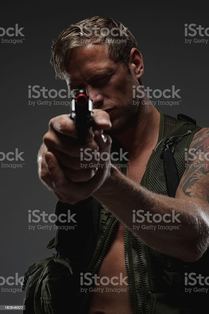 Soldier with a gun aims at you against dark background royalty-free stock photo