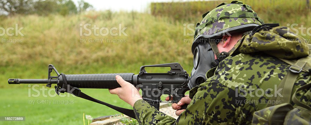 Soldier with gas mask and M16 rifle stock photo