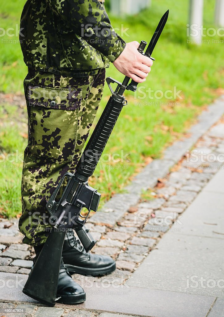 Soldier with gun guarding an entrance stock photo