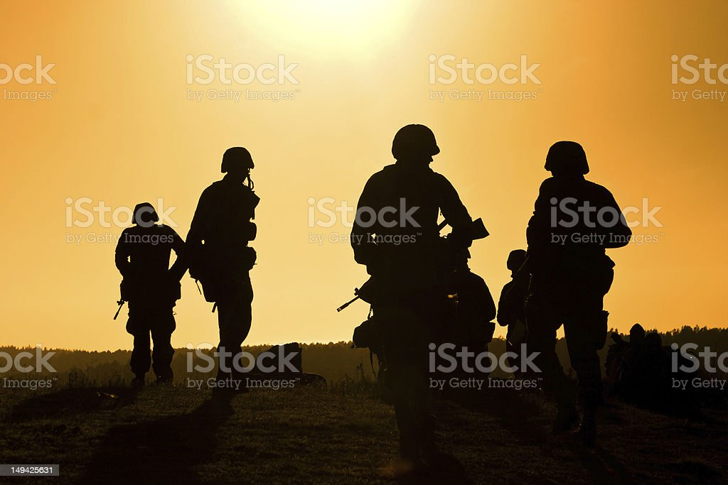 Soldiers against a sunset royalty-free stock photo