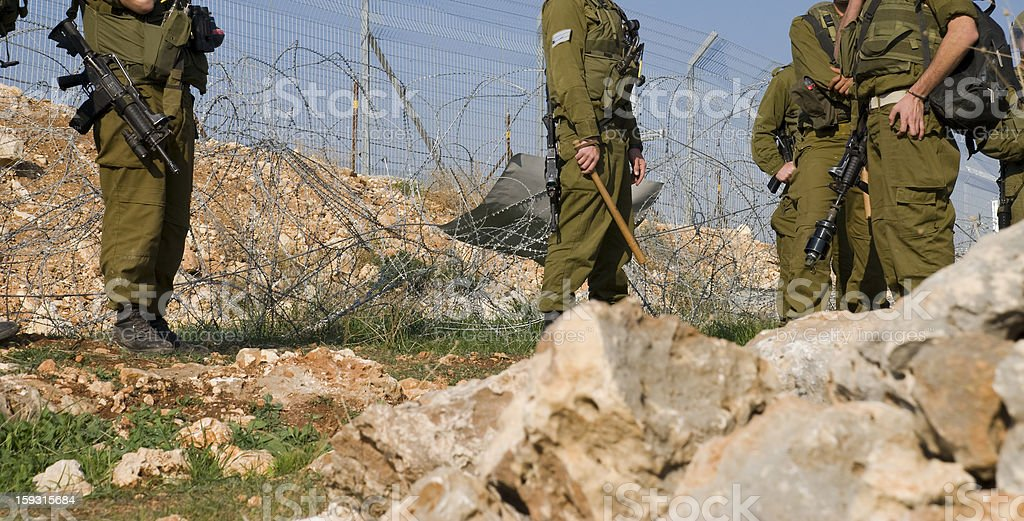 IDF soldiers by security barrier in West Bank village stock photo