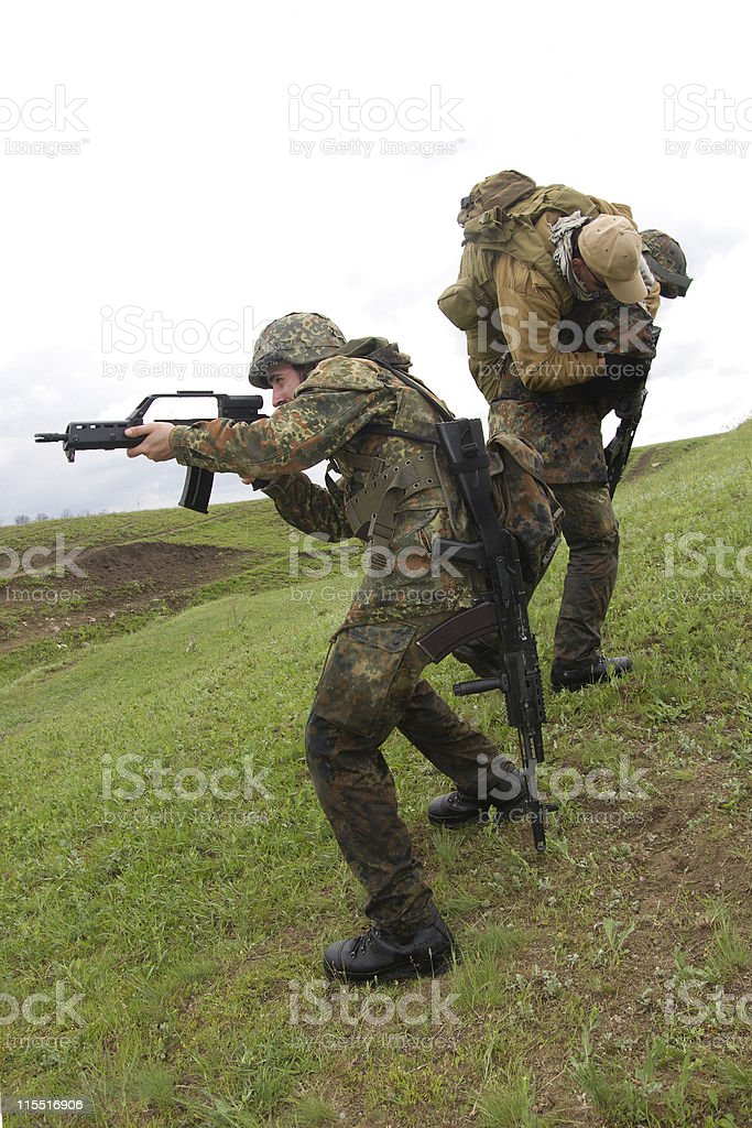 Soldiers helping their wounded partner royalty-free stock photo
