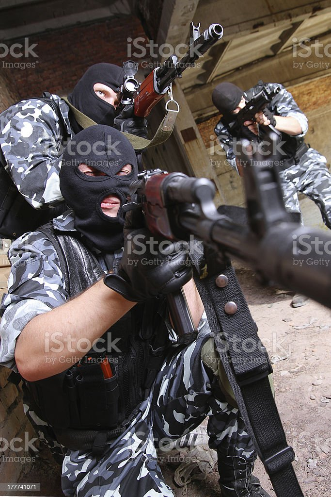 Soldiers in black masks targeting with guns royalty-free stock photo