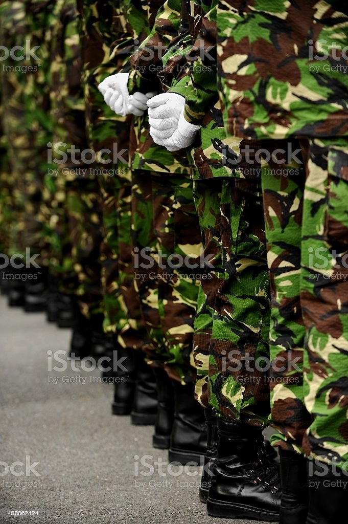 Soldiers in camouflage uniform with hands behind backs stock photo