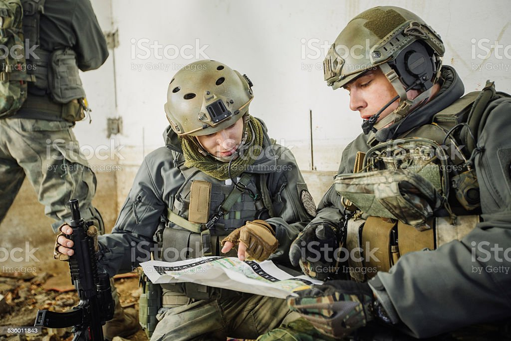 soldiers in the room looking at the map stock photo