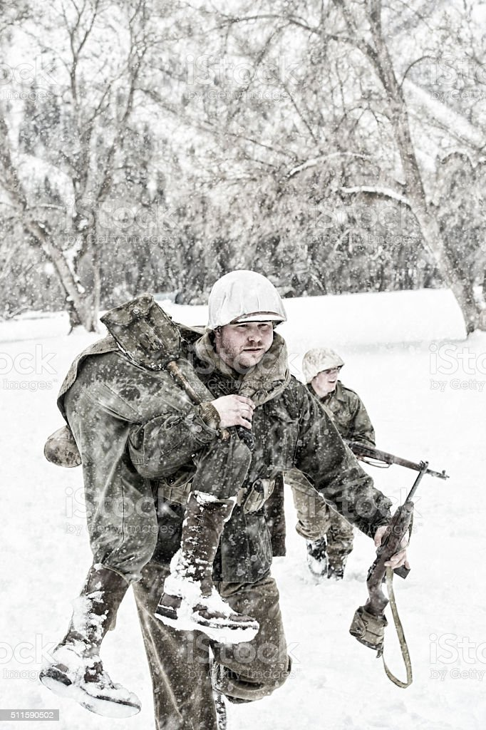 Soldiers in WWII Evacuating A Wounded Team Member stock photo