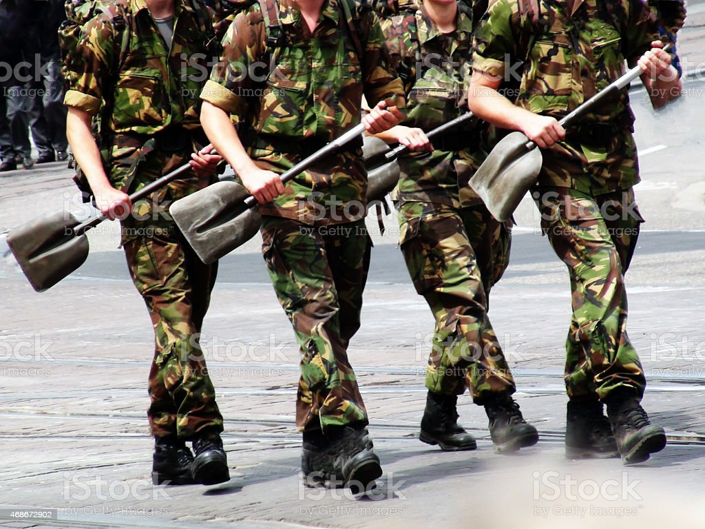 Soldiers marching with building shovel stock photo