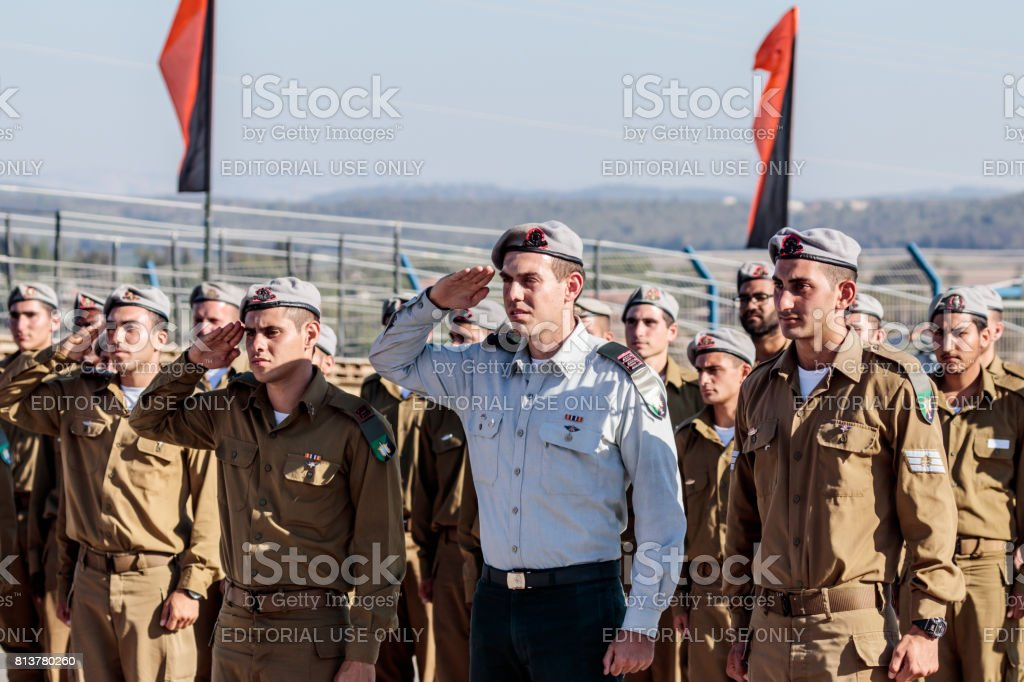 Soldiers of the Israel Defense Forces stand in a line and salute at the evening formation in Nahariya, Israel stock photo