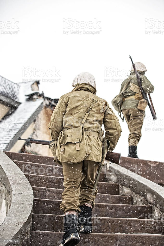 WWII US Soldiers On Patrol Climbing Stairs to Bombed Building stock photo