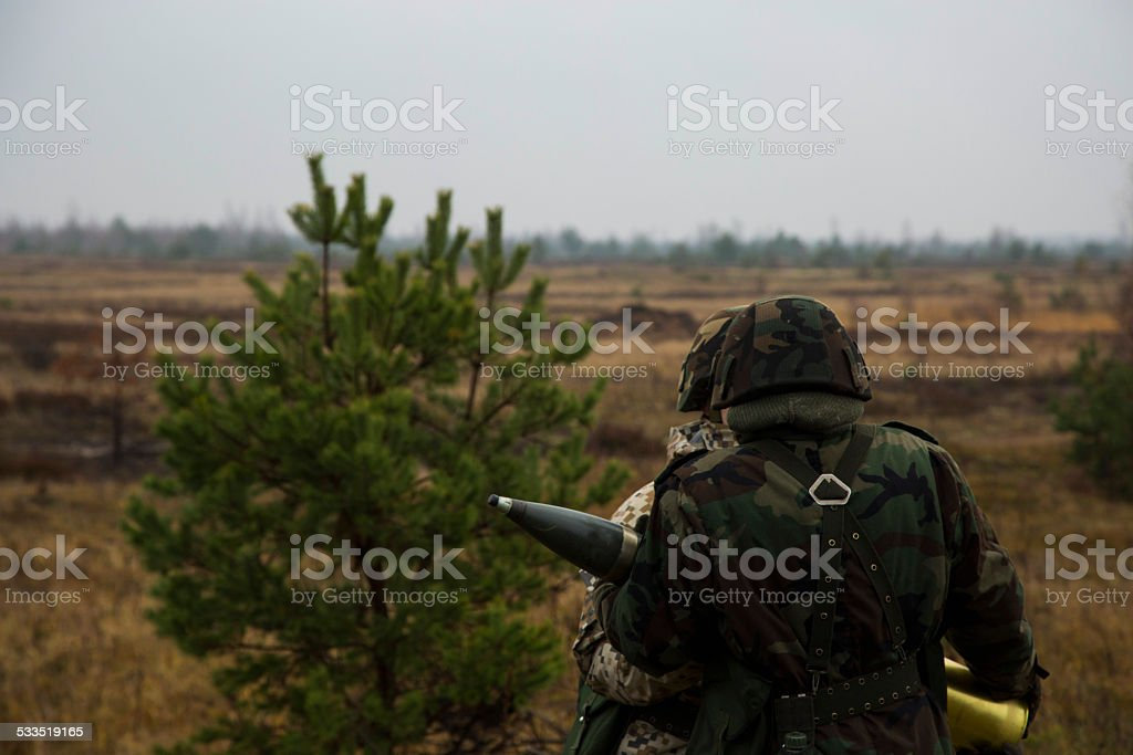 Soldiers pass artillery shell stock photo