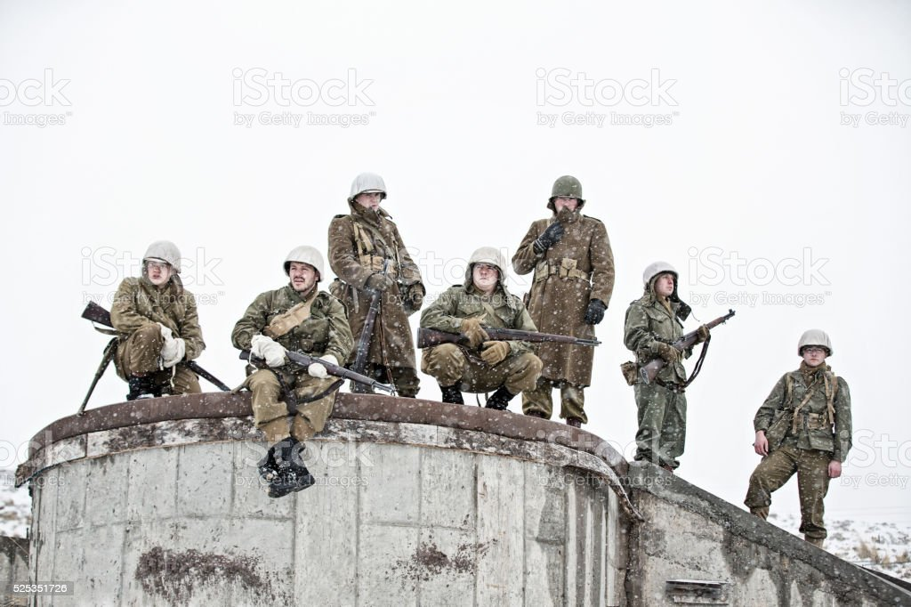 Soldiers Resting on Foundation of Bombed Building In WWII stock photo