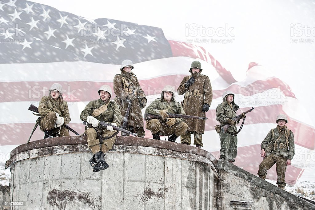 Soldiers Resting On Foundation Of Bombed Building With American Flag stock photo