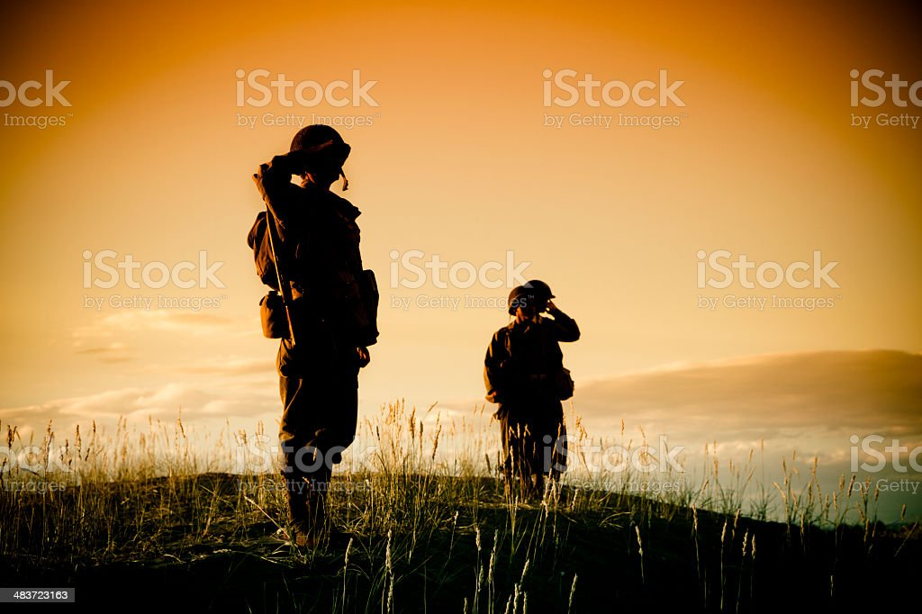 WWII Soldiers Saluting On A Hill stock photo