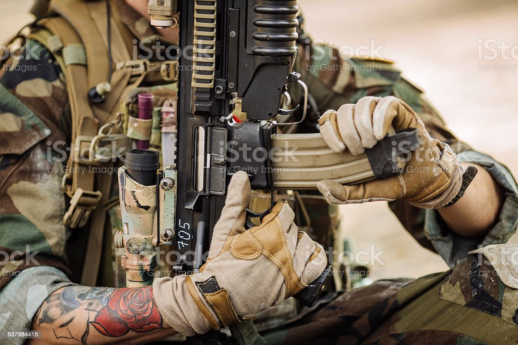 soldiers sitting and reloads his weapon stock photo