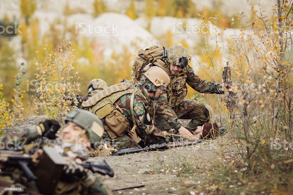 Soldiers team medic assists wounded taliban soldier stock photo