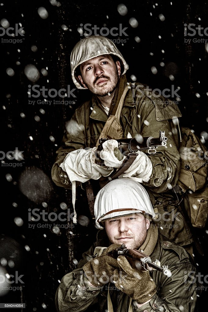 WWII Soldiers Waiting Rifle Ready In A Burned Out Building stock photo