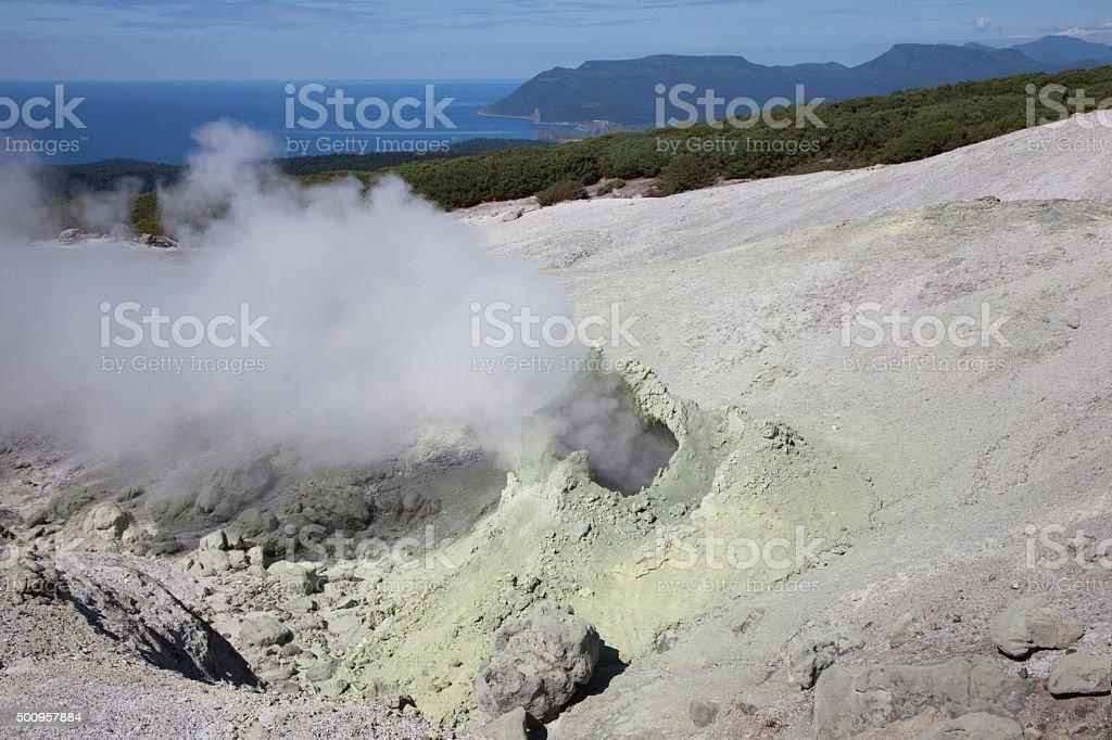 Solfatara emitting fumes amidst fumarole field stock photo