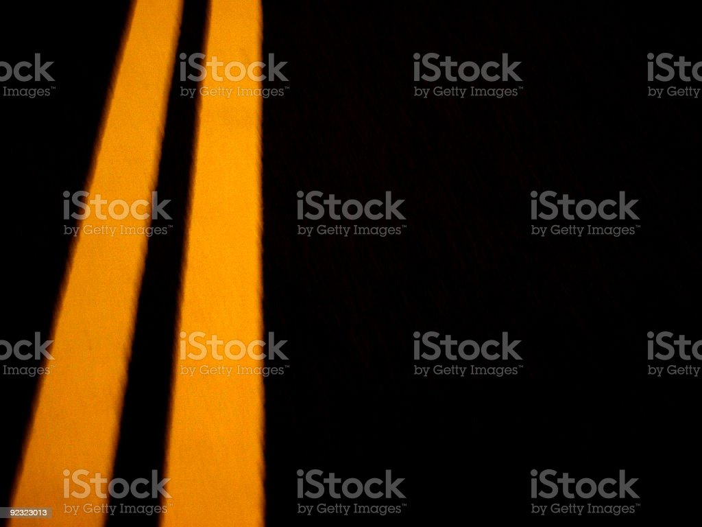 Solid yellow dividing lines on a dark black pavement royalty-free stock photo